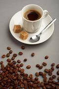 Kuva kuppi mustaa kahvia kaksi kappaletta sokeria ja ruskeat pavut lähellä Kuvituskuvat