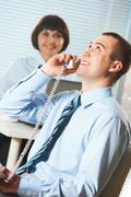 portrait of happy businessman calling with secretary on background - stock photo