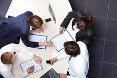 above view of several business partners discussing business plan - stock photo
