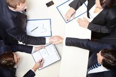 above view of business partners handshaking after signing contract - stock photo