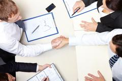 Above view of business partners handshaking after signing contract Stock Photos
