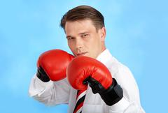 portrait of aggressive businessman wearing boxing gloves over blue background - stock photo