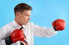 portrait of aggressive businessman in boxing gloves fighting over blue backgroun - stock photo