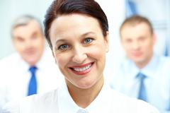 face of happy businesswoman looking at camera with two men on background - stock photo