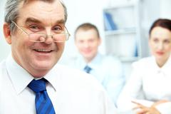 face of senior businessman looking at camera with two partners on background - stock photo