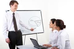 Photo of happy man commenting diagram to his colleagues who sitting at the desk Stock Photos