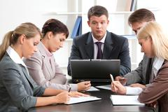 Photo of business group sitting at workplace and working with papers Stock Photos