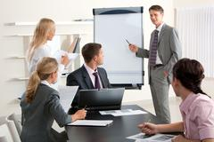 image of smart business people looking at their leader while he explaining somet - stock photo