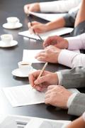 close-up of line of hands with pens over papers on the table - stock photo