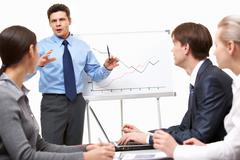 Image of confident man making presentation and interacting with the audience Stock Photos