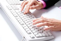 photo of female hands over white keyboard pushing its buttons during work - stock photo