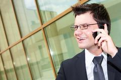 Photo of handsome employer speaking on the phone with potential business partner Stock Photos