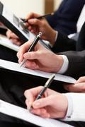 close-up of business person hand with documents writing at lecture - stock photo