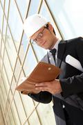 portrait of confident foreman in helmet making business plan - stock photo