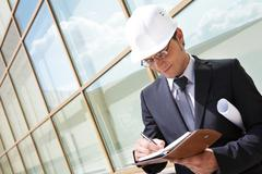 portrait of confident foreman in helmet writing business plan - stock photo