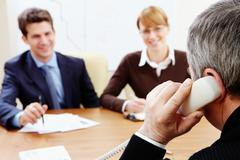rear view of aged businessman talking on the phone with his employees near by - stock photo