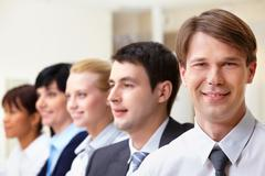 Confident businessman looking at camera on background of colleagues Stock Photos