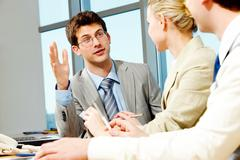 Stock Photo of portrait of businessman explaining work to his colleagues