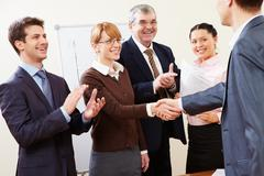 Photo of successful business partners handshaking after striking great deal with Stock Photos