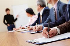 Row of business people making notes during presentation Stock Photos