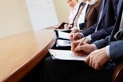 Close-up of businesspeople hands with documents writing at lecture Stock Photos