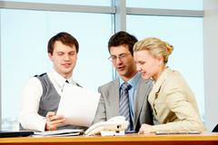 photo of three colleagues discussing business plan at workplace - stock photo