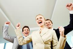 portrait of successful people raising hands with businesswoman in front - stock photo