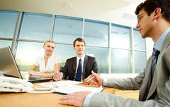 photo of businesspeople sitting at the table - stock photo
