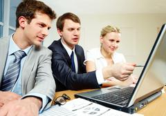 photo of businesspersons sitting at the table and working - stock photo
