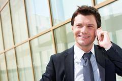 Photo of handsome employer speaking by mobile phone on sunny day Stock Photos