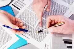 close-up of three hands with pen showing document - stock photo