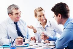 portrait of three businesspersons brainstorming during coffee break - stock photo