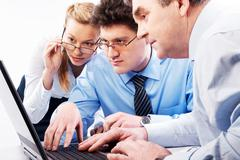 Stock Photo of photo of three businesspeople doing computer work together