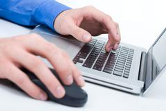 Close-up of male hands on mouse and over black keyboard of laptop during compute Stock Photos