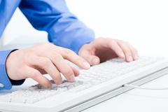 close-up of male hand touching buttons of white computer keyboard - stock photo