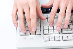 above angle of male hands touching buttons of white computer keyboard - stock photo