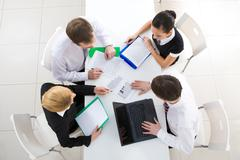 above view of friendly workteam discussing business plan at meeting - stock photo
