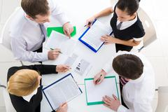 Stock Photo of above view of friendly workteam discussing business plan at meeting