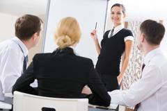 Photo of successful manager standing by whiteboard while the others listening to Stock Photos