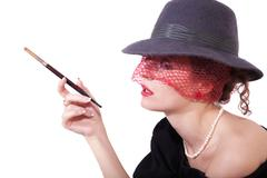 Young woman in a hat and veil with cigarette Stock Photos