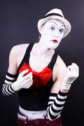theatrical mime in white hat and striped gloves - stock photo