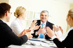 Image of senior leader surrounded by his colleagues applauding to him Stock Photos