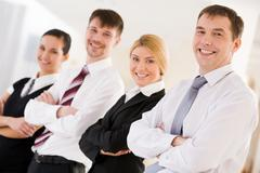 portrait of happy leader looking at camera in front of his business team - stock photo