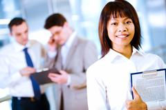 Portrait of happy businesswoman smiling at camera on background of working emplo Stock Photos