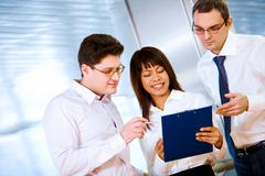 photo of confident employees looking at notes in female hand - stock photo