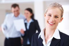 portrait of blonde businesswoman looking at camera in working environment - stock photo