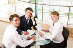 Photo of successful co-workers gathered around table and looking at camera durin Stock Photos