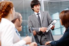 Photo of confident leader pointing at paper with diagrams during meeting Stock Photos