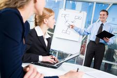 image of young manager giving a presentation to some colleagues - stock photo