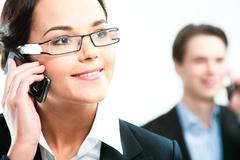 portrait of pretty businesswoman calling and looking aside - stock photo